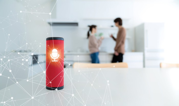 A smart speaker on a table with two people in the background.