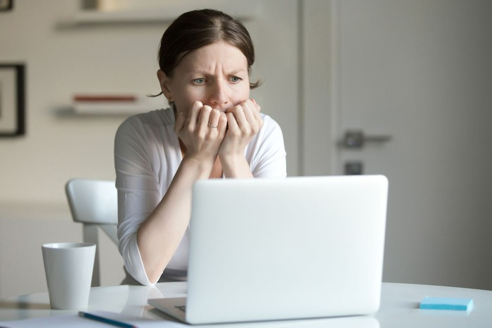 A woman puts her hands to her mouth in worry as she looks at her laptop screen.