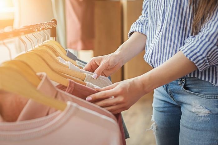 Woman thumbing through shirts hanging on a rack