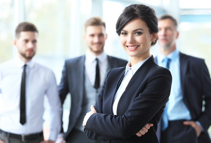 A businesswoman standing in fromt of three businessmen