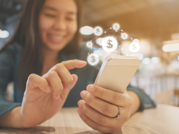 A young girl smiles and uses her smartphone with animations of dollar signs coming out of it.