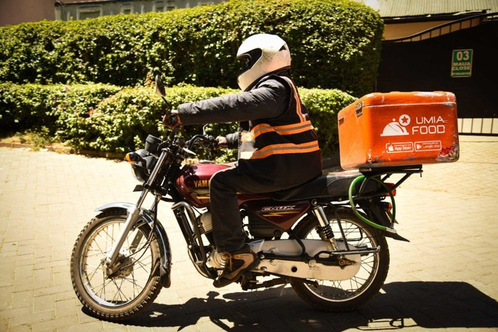 A Jumia delivery man on a motorcycle.