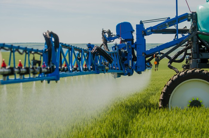 Blue tractor in a green field with crop spraying attachment on back.