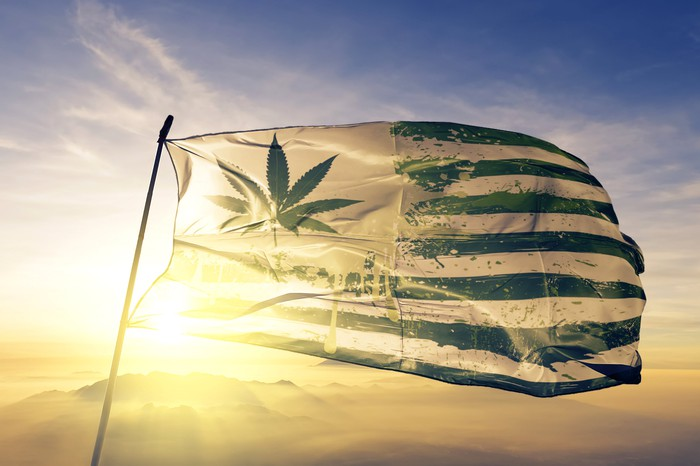 An American flag with a cannabis leaf in place of the stars blowing in the wind.