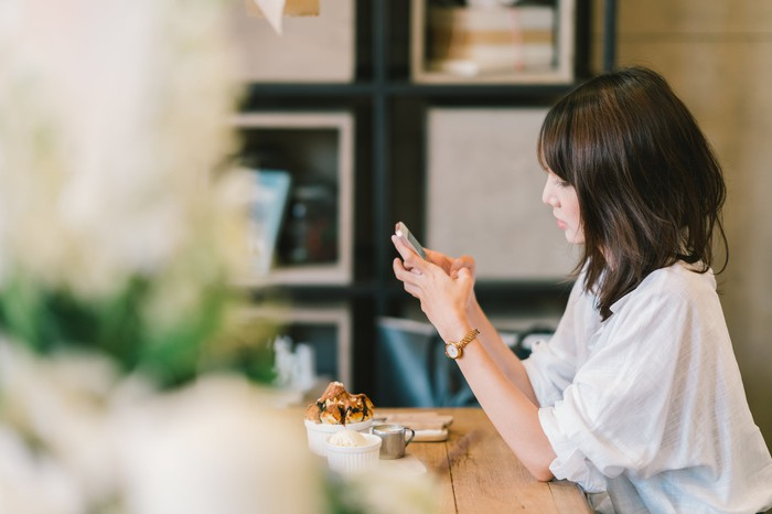 A woman looking at a smartphone at a cafe