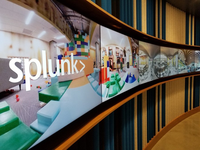 Long line of connected flat screen televisions with Splunk logo and office space displayed.