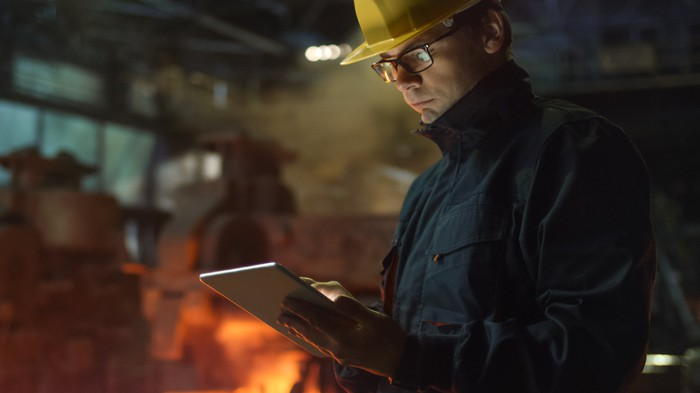 A man writing in a notebook with a steel furnace in the background.