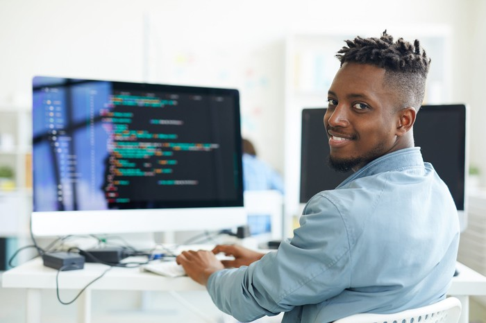 Computer programmer typing while looking at the camera