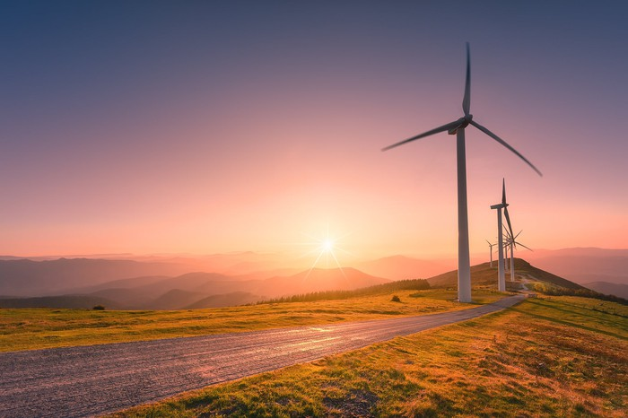 Wind turbines along a road with the sun setting in the background.