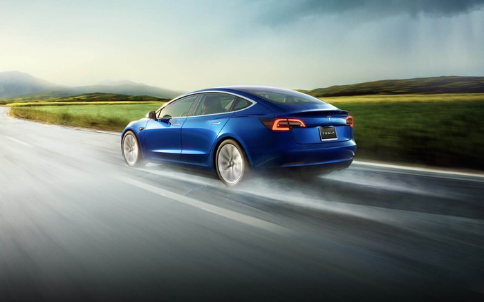 Blue Tesla Model 3 on a wet road on a cloudy day, driving through a grassy landscape.