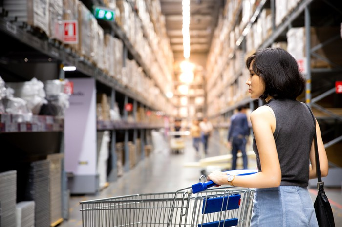 A dark haired woman wheels an empty shopping cart down an aisle of a large warehouse store looking at items.