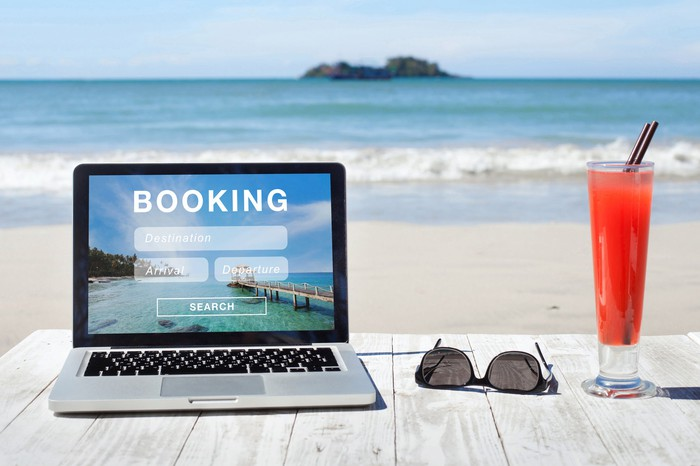 On a table at the beach, next to a tropical drink and a pair of sunglasses, a laptop shows a travel booking website.