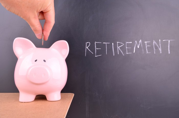 Person inserting coin into piggy bank sitting on a table in front of a blackboard with the word retirement written on it in chalk
