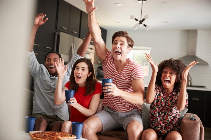 A group of twenty-something friends cheer and react to a game on TV as they drink from cups and a pizza is in front of them on a table.