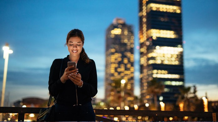 A woman holding a smartphone at dusk. City skyscrapers are in the background.