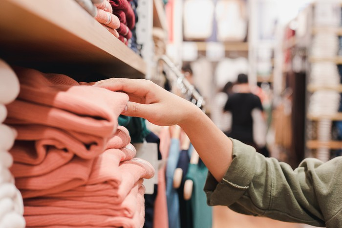 A person reaches for a shirt on a shelf in a clothing store.