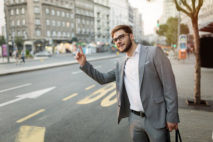Man in suit hailing a taxi