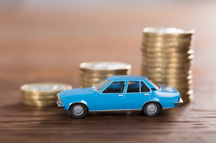 A miniature car in front of three stacks of coins.