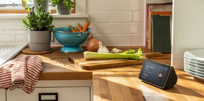 Echo Show 5 on a kitchen counter next to a cutting board with vegetables on it and a colander containing carrots