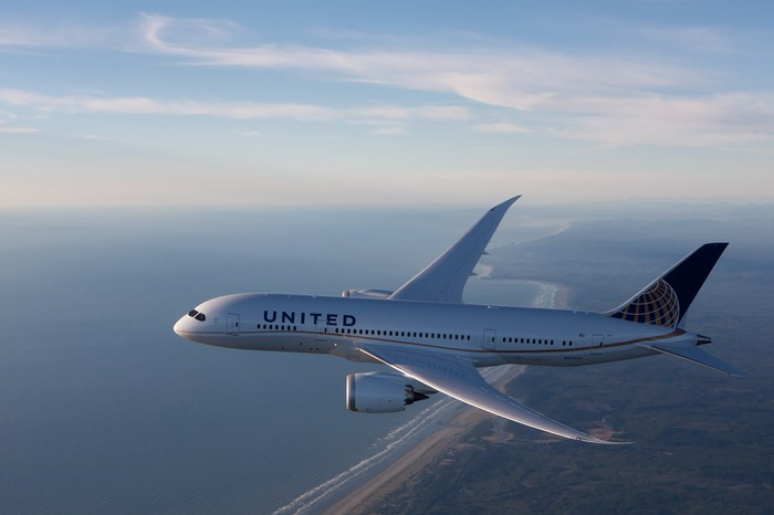 A United Airlines Boeing 787 flying over a coastline.
