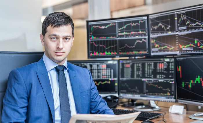 A man in a suit sitting in front of computer screens with stock information on them.