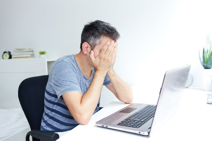 Man sitting at laptop, covering his face