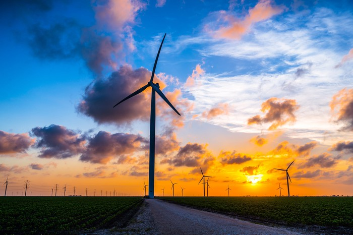 Wind turbines in a field, with the sun setting in the background.