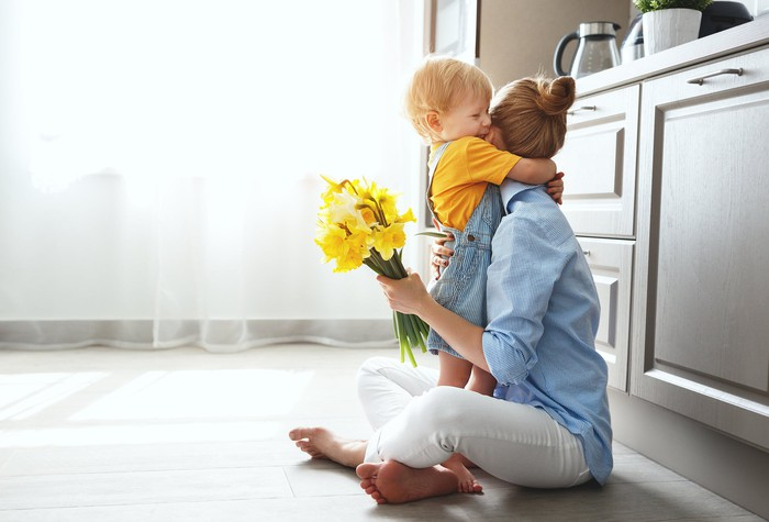 Woman sitting on floor in a kitchen, hugging young child while holding flowers.