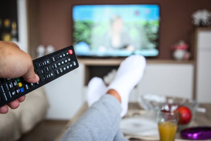 A person watches TV with their feet up on the coffee table.