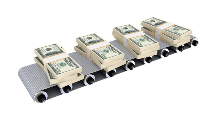 A conveyor belt with four piles of cash on it.