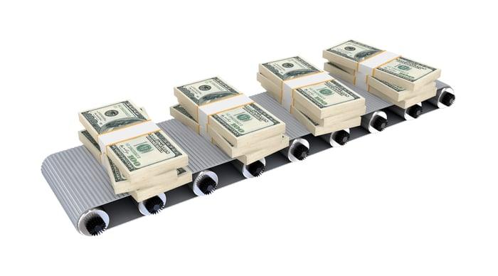 Un tapis roulant avec quatre piles de billets.