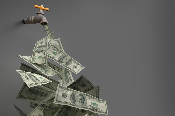 Un robinet avec de l'argent qui en sort.