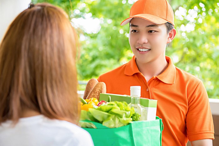 A young delivery man dressed in orange delivers groceries in a woman's doorway.