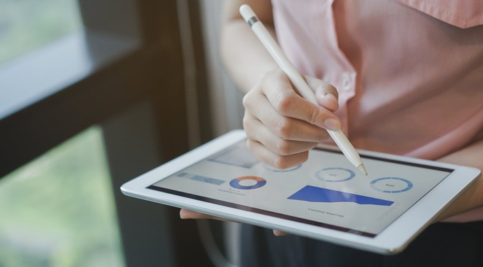 Close up on businesswoman's hand using stylus pen for writing on tablet screen