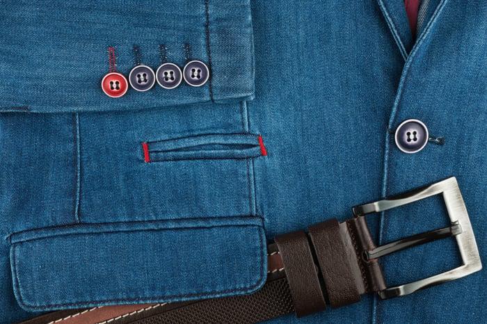 A leather belt rests on a denim jacket.