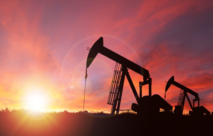 Two oil pumps with a bright rising or setting sun on the horizon