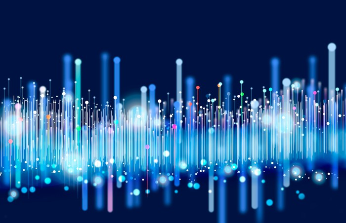 Colorful illuminated bright vertical lines on a black background symbolize big data transfer over a network.
