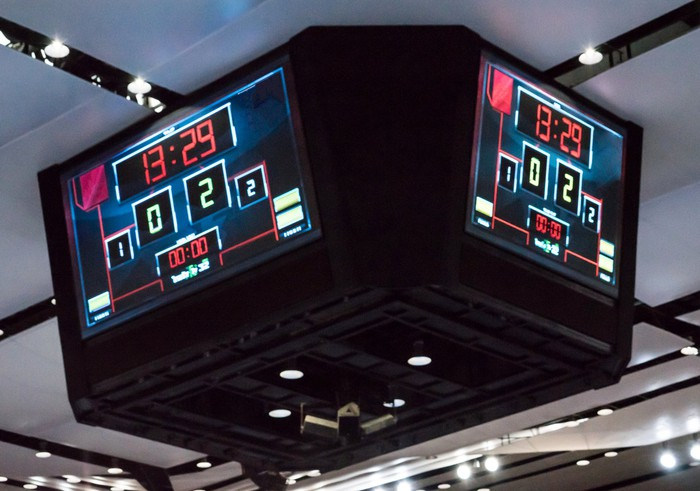A modern scoreboard, attached to the ceiling of an indoor sports arena.
