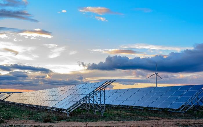 Solar panels and a wind turbine at dusk.