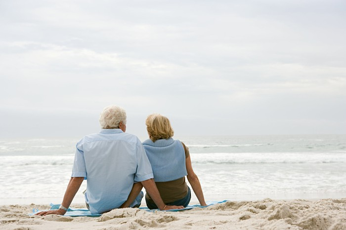 Senior couple sitting together on the beach.