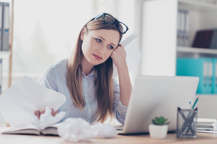 Woman sitting at laptop, resting her face on her hand