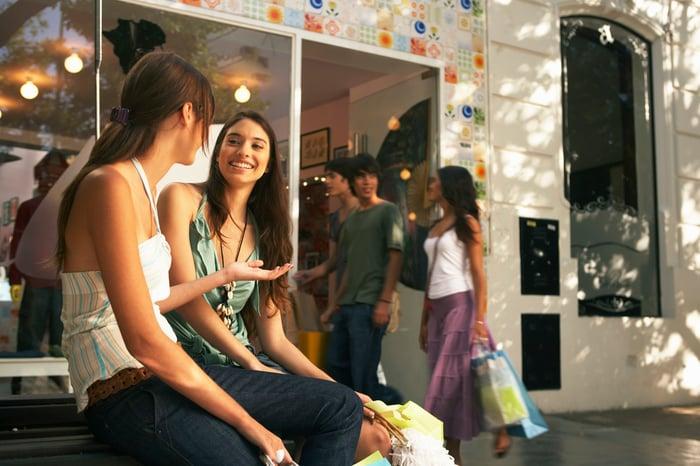 Two teenage girls sitting inside a mall.