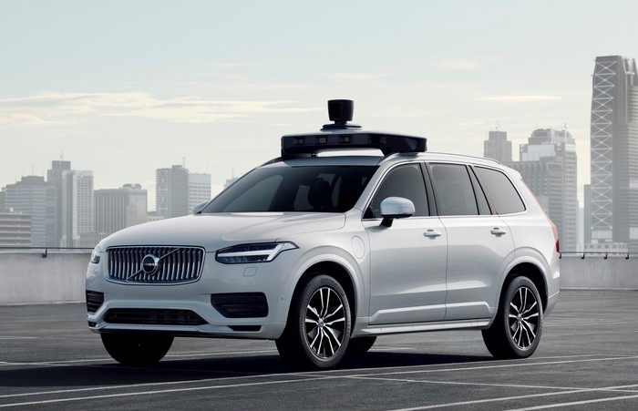 A white Volvo SUV with visible self-driving sensor hardware.