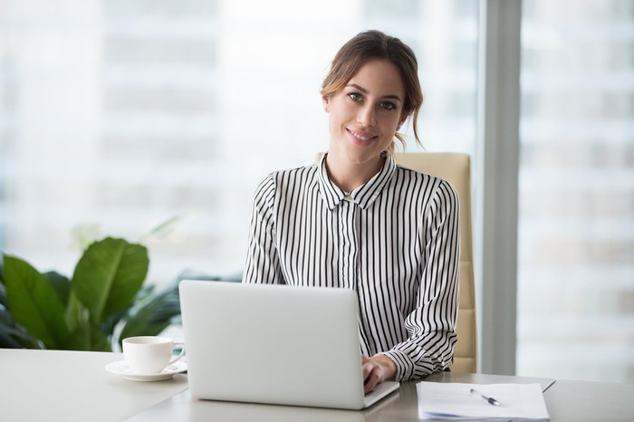 A woman in business casual attire sits at a desk, with an open laptop in front of her and a picture window behind her.