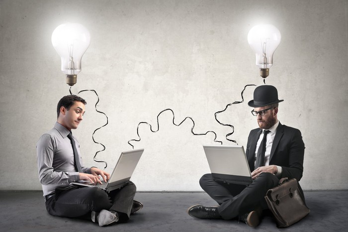 Two men sitting on the floor using laptops. Light bulbs are shining above their heads.
