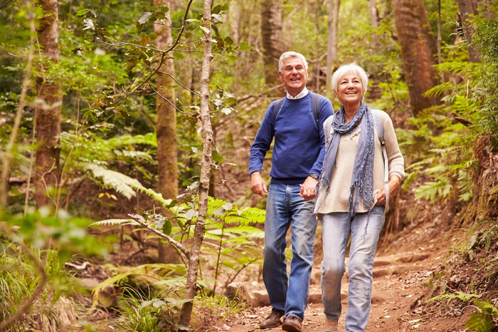 Senior couple walking on a wooded trail.