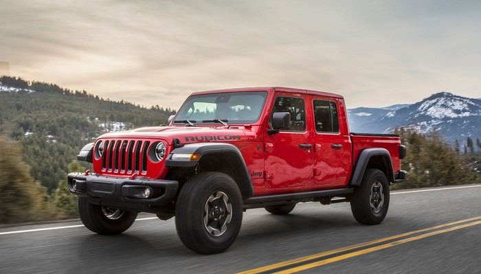 A red Jeep Gladiator, an off-road pickup truck based on the iconic Jeep Wrangler, on a mountain road