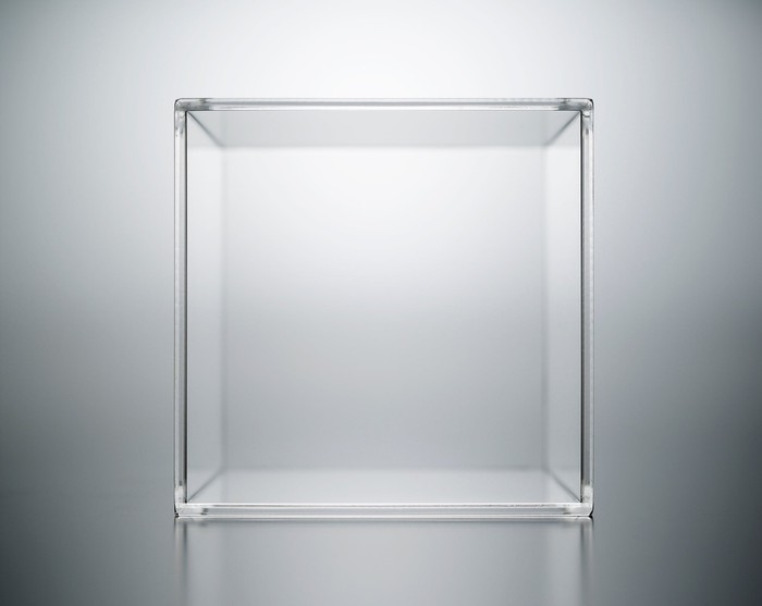 A transparent acrylic box on a luminous grey background.