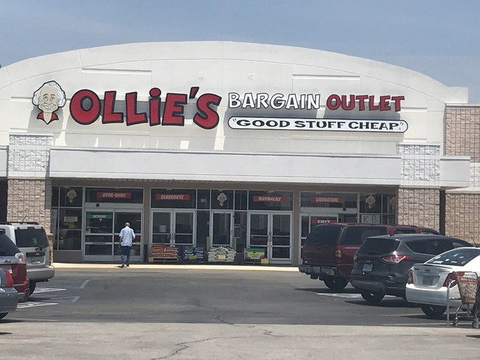 Ollie's Bargain Outlet store seen from parking lot, with several cars and a shopper.