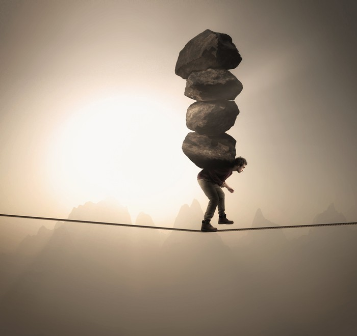 Man walking tightrope carrying four boulders on his back
